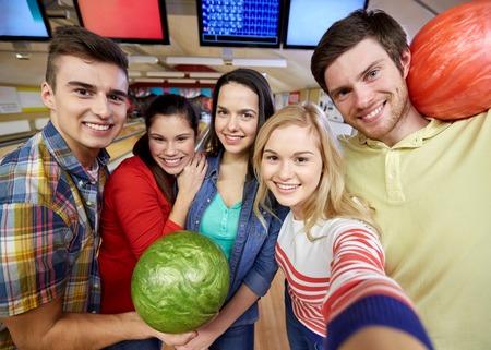 bolos: la gente, el ocio, el deporte, la amistad y el concepto de entretenimiento - amigos felices que toman Autofoto con c�mara o un tel�fono inteligente en el club de bolos