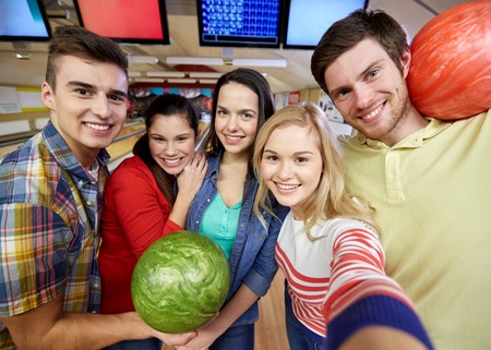 people, leisure, sport, friendship and entertainment concept - happy friends taking selfie with camera or smartphone in bowling club photo