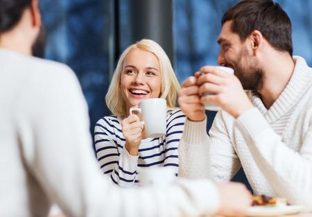 hombre tomando cafe: gente, ocio, comunicaci�n, comiendo y bebiendo concepto - amigos felices reuniones y beber t� o caf� en el caf�