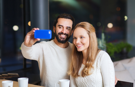 people, leisure, communication, eating and drinking concept - happy couple with smartphone taking selfie at cafe photo