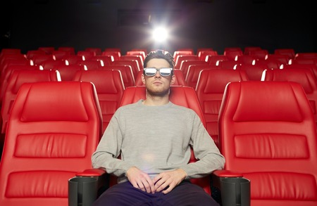 alone man: cinema, technology, entertainment and people concept - young man with 3d glasses watching movie alone in empty theater auditorium
