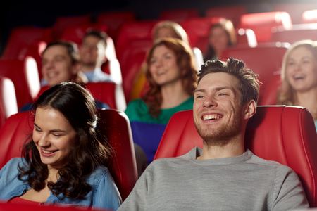 family movies: cinema, entertainment and people concept - happy friends watching comedy movie in theater