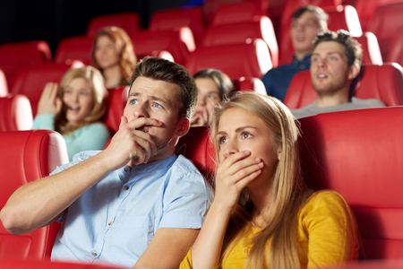 entertainment: cinema, entertainment and people concept - happy friends watching horror, drama or thriller movie in theater
