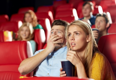 movies: cinema, entertainment and people concept - couple drinking soda and watching horror, drama or thriller movie in theater