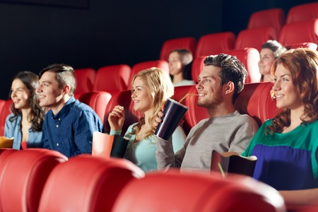 at the theater: cinema, entertainment and people concept - happy friends watching movie in theater