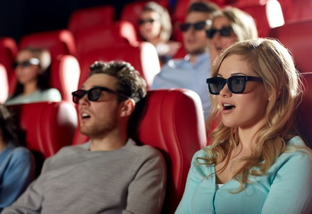 3d scary: cinema, technology, entertainment and people concept - friends with 3d glasses watching horror or thriller movie in theater Stock Photo