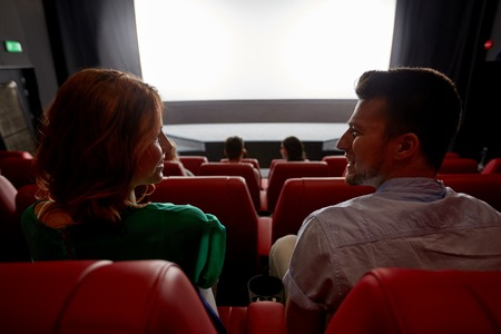 cinema, entertainment and people concept - happy friends watching movie in theater from back Archivio Fotografico