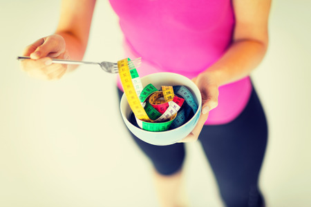 to the diet: sport and diet concept - woman hands holding bowl with measuring tape Stock Photo