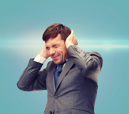 loud: business and office, stress, problem, crisis, loud noise concept - stressed buisnessman or teacher closing ears