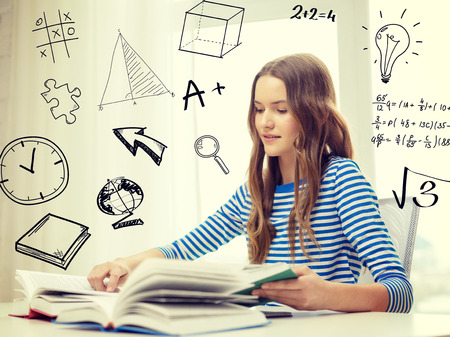 exam preparation: education and home concept - smiling student girl sitting at table and reading books