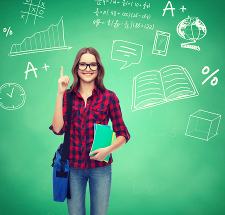 education, happiness and people concept - smiling student girl showing thumbs up over green board background photo