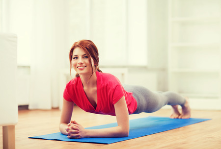 redhead: fitness, home and diet concept - smiling redhead teenage girl doing plank at home
