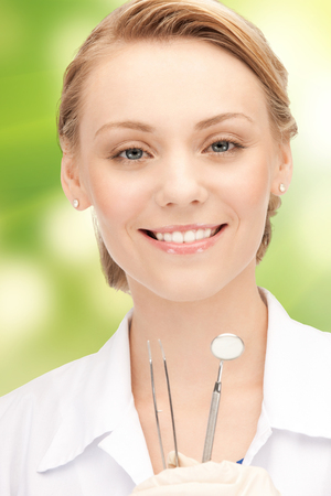 stomatology: people, medicine, stomatology and healthcare concept - happy young female dentist with tools over green background