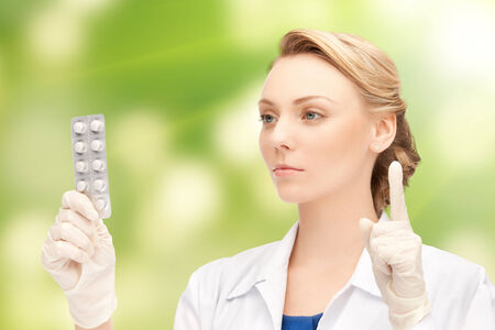 contraception: people, medication and warning gesture concept - young female doctor with pills pointing finger up over green background