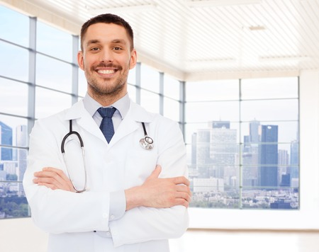 male doctor: healthcare, profession, people and medicine concept - smiling male doctor with stethoscope in white coat over clinic room background
