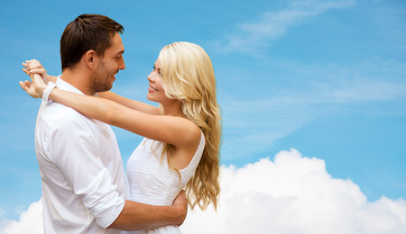 summer holidays, people, love and dating concept - happy couple hugging over cloud and blue sky background photo