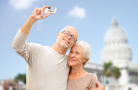 age, tourism, travel, technology and people concept - senior couple with camera taking selfie on street over washington white house background photo