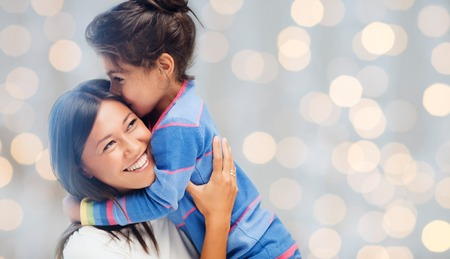 asian happy family: people, happiness, love, family and motherhood concept - happy mother and daughter hugging over holiday lights background Stock Photo
