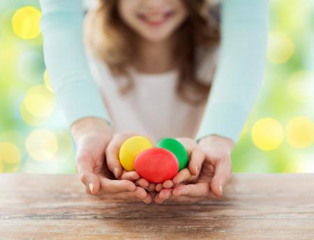 familia cristiana: Pascua, familia, gente, fiestas y la infancia concepto - huevos de cerca de una niña feliz y manos de la madre explotación de colores sobre fondo verde luces Foto de archivo