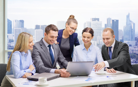 business, technology, teamwork and people concept - smiling business team with laptop computers, documents and coffee having discussion over office background