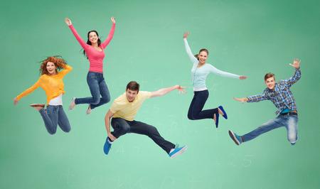 행복, 자유, 우정, 교육, 사람들 개념 - 녹색 보드 배경 위에 공중에서 점프 웃는 청소년의 그룹
