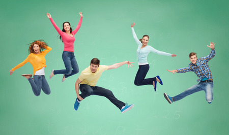 group cooperation: happiness, freedom, friendship, education and people concept - group of smiling teenagers jumping in air over green board background