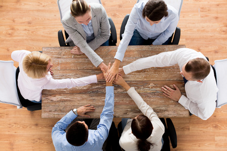 business, people, cooperation and team work concept - close up of creative team sitting at table and holding hands on top of each other in office Banco de Imagens
