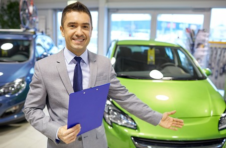 sale: auto business, car sale, consumerism and people concept - happy man at auto show or salon
