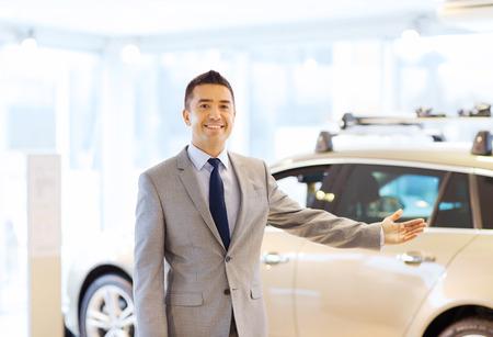 invitando: negocio de autos, venta de coche, el consumismo y el concepto de la gente - hombre feliz en su salón del automóvil o el salón