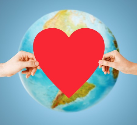 world peace: people, love, health, environment and charity concept - close up of woman hands holding red heart over earth globe and blue background