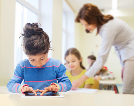 classroom: education, elementary school, technology and children concept - little student girl with tablet pc over classroom and teacher background Stock Photo