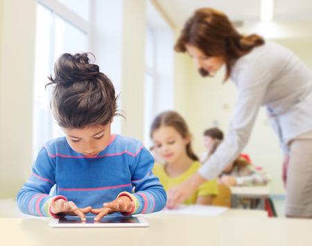 onderwijs, basisschool, technologie en kinderen concept - klein student meisje met tablet pc dan klas en leraar achtergrond