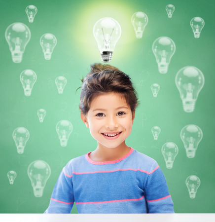 asian preteen: education, energy saving, children and people concept - smiling little girl over green chalk board background and light bulbs Stock Photo