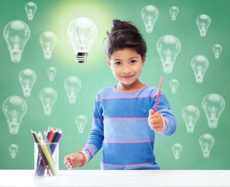Bildung, Schule, Kinder, Kreativität und glückliche Menschen Konzept - glückliches kleines Mädchen Zeichnung mit Farbstiften über grüne Kreidetafel Hintergrund und Glühbirnen