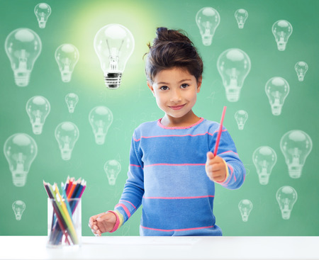 education, school, children, creativity and happy people concept - happy little girl drawing with coloring pencils over green chalk board background and light bulbs Stock Photo