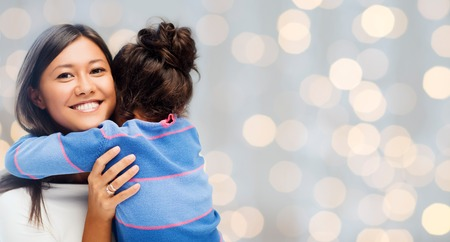 people, happiness, love, family and motherhood concept - happy mother and daughter hugging over holiday lights background Stock Photo