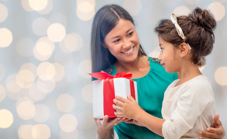 preteen asian: people, holidays, christmas and family concept - happy mother and daughter giving and receiving gift box over holiday lights background