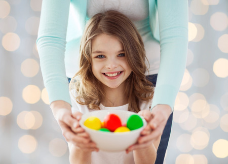orthodox: easter, family, people, holiday and childhood concept - close up of happy girl and mother hands holding bowl with colored eggs over lights background Stock Photo
