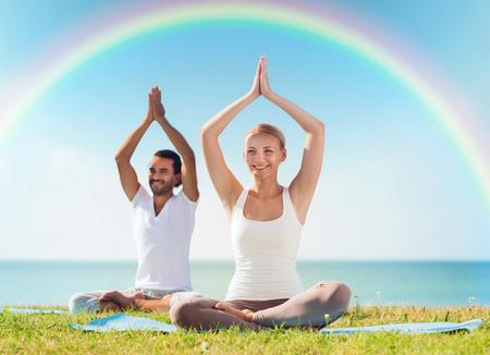 manos levantadas al cielo: deporte, fitness, yoga y concepto de la gente - sonriente pareja meditando y sentados sobre esteras con las manos levantadas sobre el mar y el arco iris en el cielo azul de fondo Foto de archivo