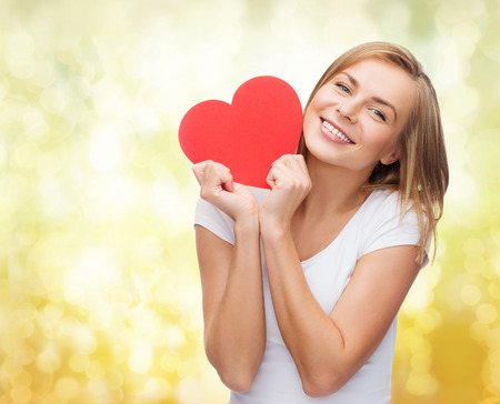 happiness, health, people, holidays and love concept - smiling young woman in white t-shirt holding red heart over yellow lights background