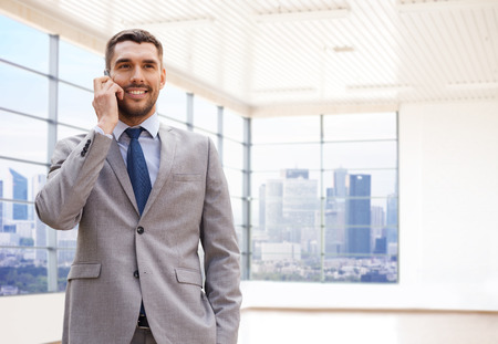 on call: business, people and office concept - happy young businessman calling on smartphone over office room or new apartment background