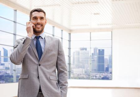 llamando: negocio, la gente y el concepto de oficina - joven empresario feliz llamando en el teléfono inteligente más de oficina o sala de fondo nuevo apartamento Foto de archivo