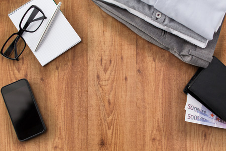 business, style, clothes and objects concept - close up of formal male clothes and personal stuff on wooden table at home Stock Photo