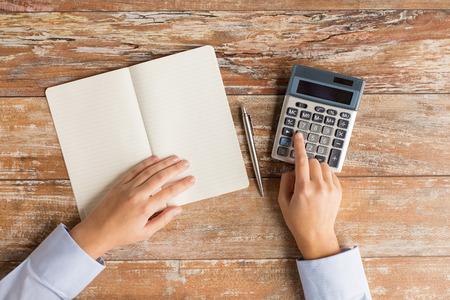 ビジネス、教育、人と技術のコンセプト - 電卓、ペン表上でノートブックと女性の手のクローズ アップ