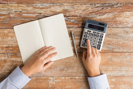 calculator: business, education, people and technology concept - close up of female hands with calculator, pen and notebook on table