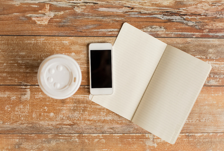 disposable: business, education, objects and technology concept - close up of notebook, coffee paper cup and smartphone on table
