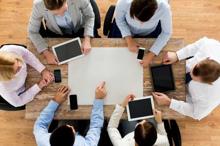 tecnología informatica: negocio, la gente, la tecnología y el trabajo en equipo concepto - cerca de equipo creativo con el papel en blanco, teléfonos inteligentes y computadoras tablet pc sentado a la mesa en la oficina Foto de archivo