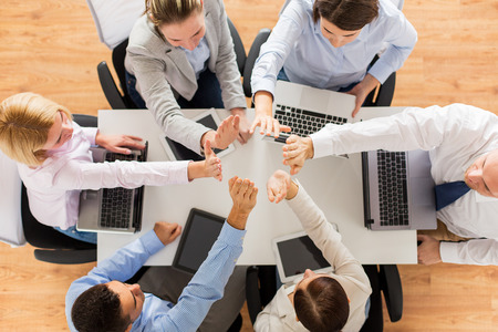 high tech: business, people, technology and team work concept - close up of creative team with laptop and tablet pc computers showing high five gesture and sitting at table in office