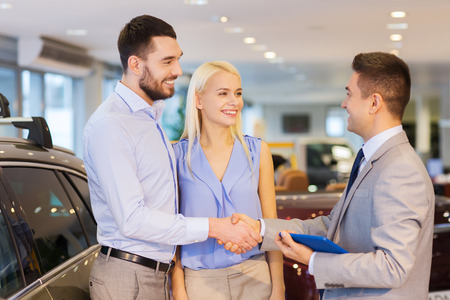 car show: auto business, car sale, technology, gesture and people concept - happy couple with car dealer shaking hands in auto show or salon