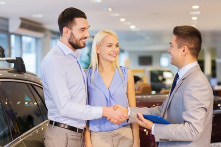 autozaken, auto verkoop, technologie, gebaar en mensen concept - gelukkig paar met autohandelaar handen schudden in autoshow of salon Stockfoto